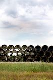 Long Pipe Stacked Next to Highway. Long large pipe stacked beside highway for construction in the vertical or portrait view Royalty Free Stock Photos