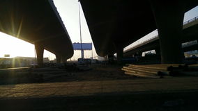 Long pipes under the bridge at afternoon stock footage