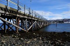 Long pont étroit en voiture reliant l'île deux de l'île de baleine et de haak ensemble au-dessus du fjord bleu et le fond neigeux Photographie stock libre de droits