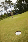 Long putt. Man attempting long putt, focus on hole in foreground Stock Images