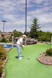 Long Putt On Mini Golf Course. Lady on a miniature golf course trying to sink a long putt Royalty Free Stock Photography