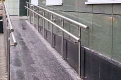 Long ramp. Metal smooth handrails. Building wall. Gray light color Royalty Free Stock Image