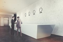 Long reception desk, clocks, side, concrete, men Stock Photography