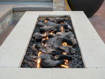 Long, rectangular fire pit sitting in open air plaza royalty free stock photography