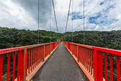 Long red bridge and forest with cloudy sky background in Kamikawa Otaki Waterfall Park, Kagoshima, Kyushu, Japan royalty free stock photos