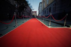 Long red carpet between rope barriers on entrance. Entry. red carpet is traditionally used to mark the route taken by heads of state on ceremonial and formal stock image