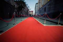 Long red carpet between rope barriers on entrance. Entry. red carpet is traditionally used to mark the route taken by heads of state on ceremonial and formal stock images