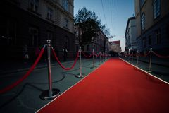 Long red carpet between rope barriers on entrance. Entry. red carpet is traditionally used to mark the route taken by heads of state on ceremonial and formal stock photo