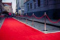 Long red carpet between rope barriers on entrance. Entry. red carpet is traditionally used to mark the route taken by heads of state on ceremonial and formal royalty free stock image