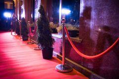 Long red carpet between rope barriers on entrance. Red Carpet Fashion Awards is a celebrity fashion website which chronicles the ensembles from runways and red stock photo