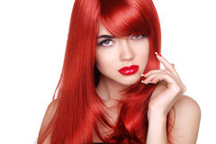 Long red hair. Fashion beautiful girl with makeup, glossy wavy h Stock Photos