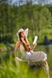 Long red hair romantic woman relax by lake Stock Images