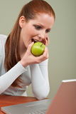 Long red hair woman biting apple at office Stock Photos