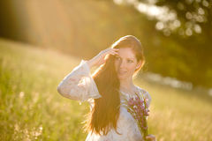 Long red hair woman in romantic sunset meadow Royalty Free Stock Images