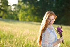 Long red hair woman in romantic sunset meadow Stock Images