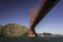 Long red span of Golden Gate bridge viewed from sailboat passing underneath Stock Image