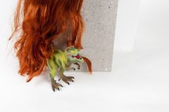 Long red wig cinder block and trex. A long red wig put on a gray cinderblock with a figurine dinosaur hidding behind on a white background. Minimal funny and Royalty Free Stock Photos