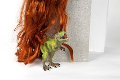 Long red wig cinder block and trex. A long red wig put on a gray cinderblock with a figurine dinosaur hidding behind on a white background. Minimal funny and Royalty Free Stock Photo