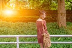 Long regard asiatique de dame de cheveux de retour et grand sourire, robe en rouge occasionnel Image stock