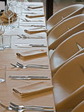 Long restaurant table prepared. With wine water glasses napkins and silver wares Royalty Free Stock Photos
