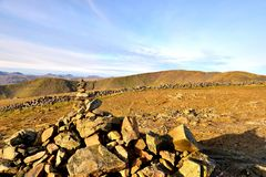 Sunlight on the marker cairn of Dove Crag. The long ridgeline of Fairfield to Great Rigg Royalty Free Stock Photography