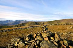 Sunlight on the marker cairn of Dove Crag. The long ridgeline from Heron Pike to Great Rigg Stock Images