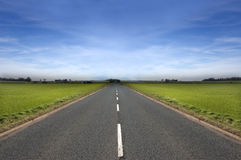 Long Road. Stretching out into the distance under a dramatic blue sky royalty free stock photos