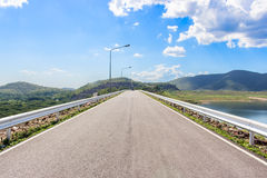 Long road ahead. Mountain. Blue sky. White clouds. Royalty Free Stock Photo