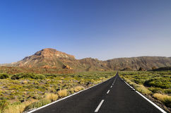 Long road ahead. Long stretch of desert highway that disappears into the Mountains Royalty Free Stock Photos