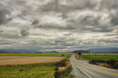 Long road cuts across valley, under looming clouds royalty free stock photos