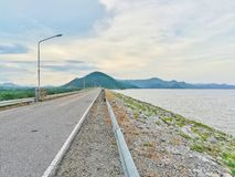 Long road, lake and mountain in cloudy day Royalty Free Stock Photography