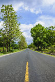 Long road. Passes through green countryside Royalty Free Stock Images