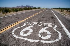 Long road with a Route 66 logo painted on it Stock Photo