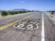 Long road with a Route 66 sign painted on it Royalty Free Stock Photos