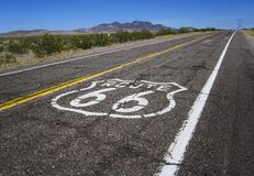 Long road with a Route 66 sign painted on it Stock Photos