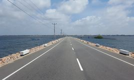 Road with water on either side. Long road through the sea Stock Images