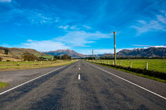 Long road stretching out to dry mountain Stock Images