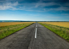 Long road stretching out into the wheat fields. Highway in the ukrainian prairie Stock Photo