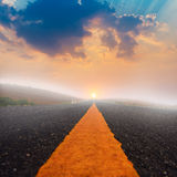 Long road and sunset with sun rays Stock Images
