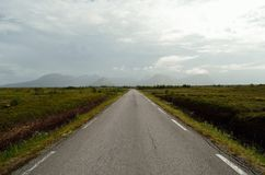 Long road throug flat landscape with mountain and fog. In backdrop royalty free stock photo