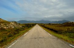Long road throug flat landscape with mountain and fog. In backdrop royalty free stock photography