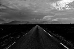 Long road throug flat landscape with mountain and fog. In backdrop stock images