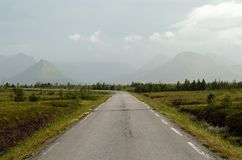 Long road throug flat landscape with mountain and fog. In backdrop royalty free stock images