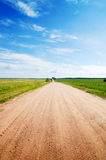 Long road to green fields. Stock Photo
