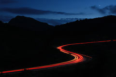 Long road to home. Night roads in the mountains with a stream of cars Stock Photo