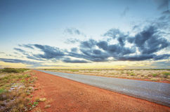 Long Road To The Horizon. A long, straight bitumen road makes its way through the dry, red desert Royalty Free Stock Photo