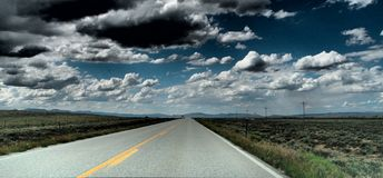 Long Road to Nowhere. Two lane road with dramatic clouds Stock Photography