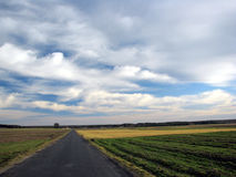 Long road under clouds Stock Photo