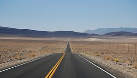 Long road. With yellow line in the middle in the desert Royalty Free Stock Photo