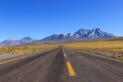 Long road with yellow lines and Mountains stock images